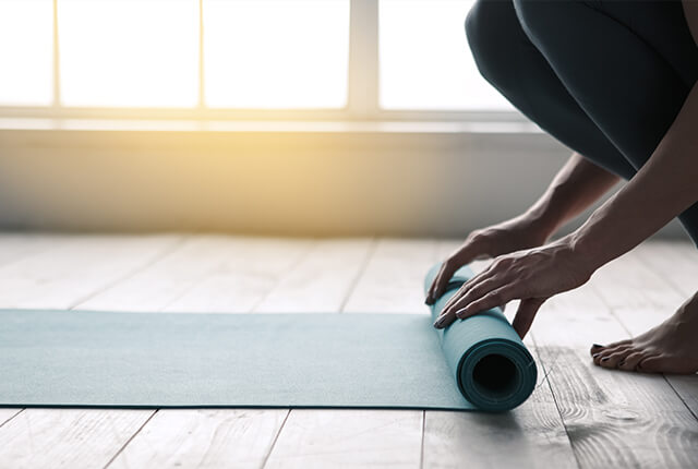 A photo of a woman unrolling an exercise mat