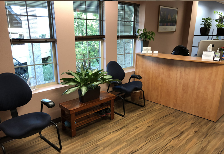 Photo of the reception area with a front desk and chairs at the Egoscue clinic in Austin, Texas