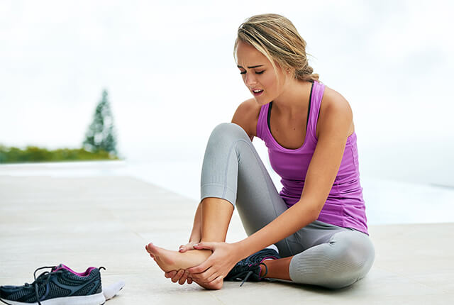 Photo of a woman in athletic clothes rubbing her foot