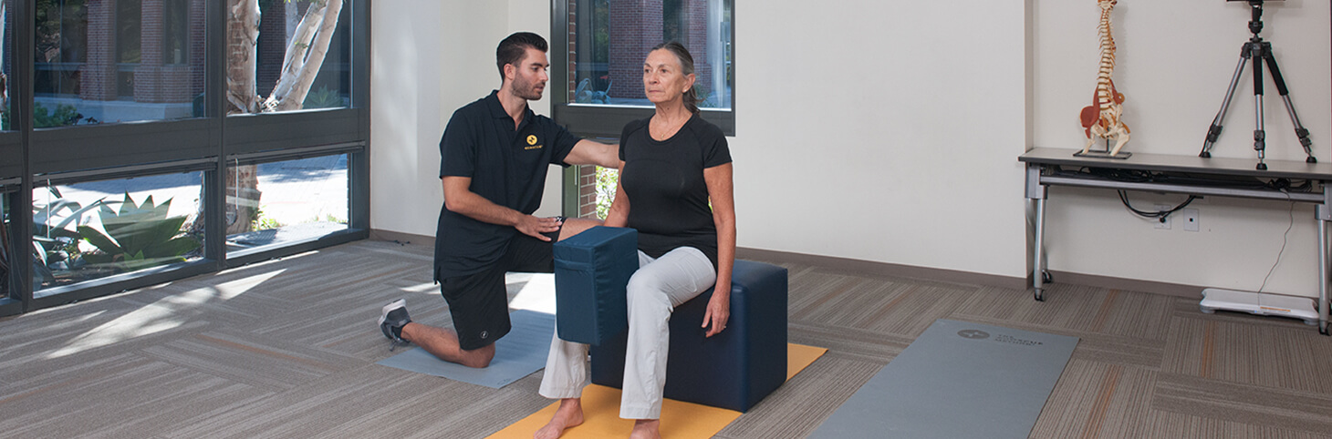 Photo of a woman doing knee exercises with an Egoscue therapist