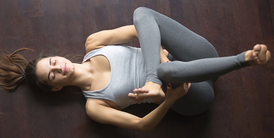 Photo of a woman in athletic clothes performing a leg stretch on a wooden floor