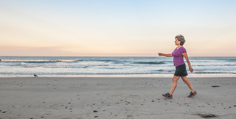 Photo of a woman in athletic clothes walking on a beach