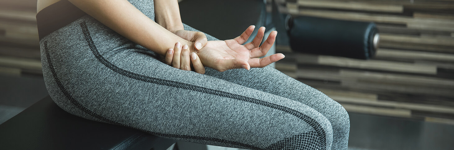 Photo of a woman in athletic clothes sitting on an exercise bench and holding her wrist