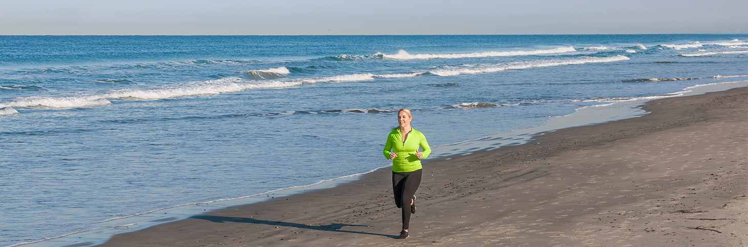 Photo of a woman in athletic clothes jogging on a beach