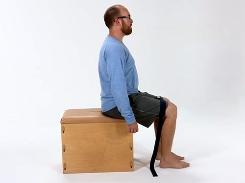 Photo of a man performing sitting abductor presses